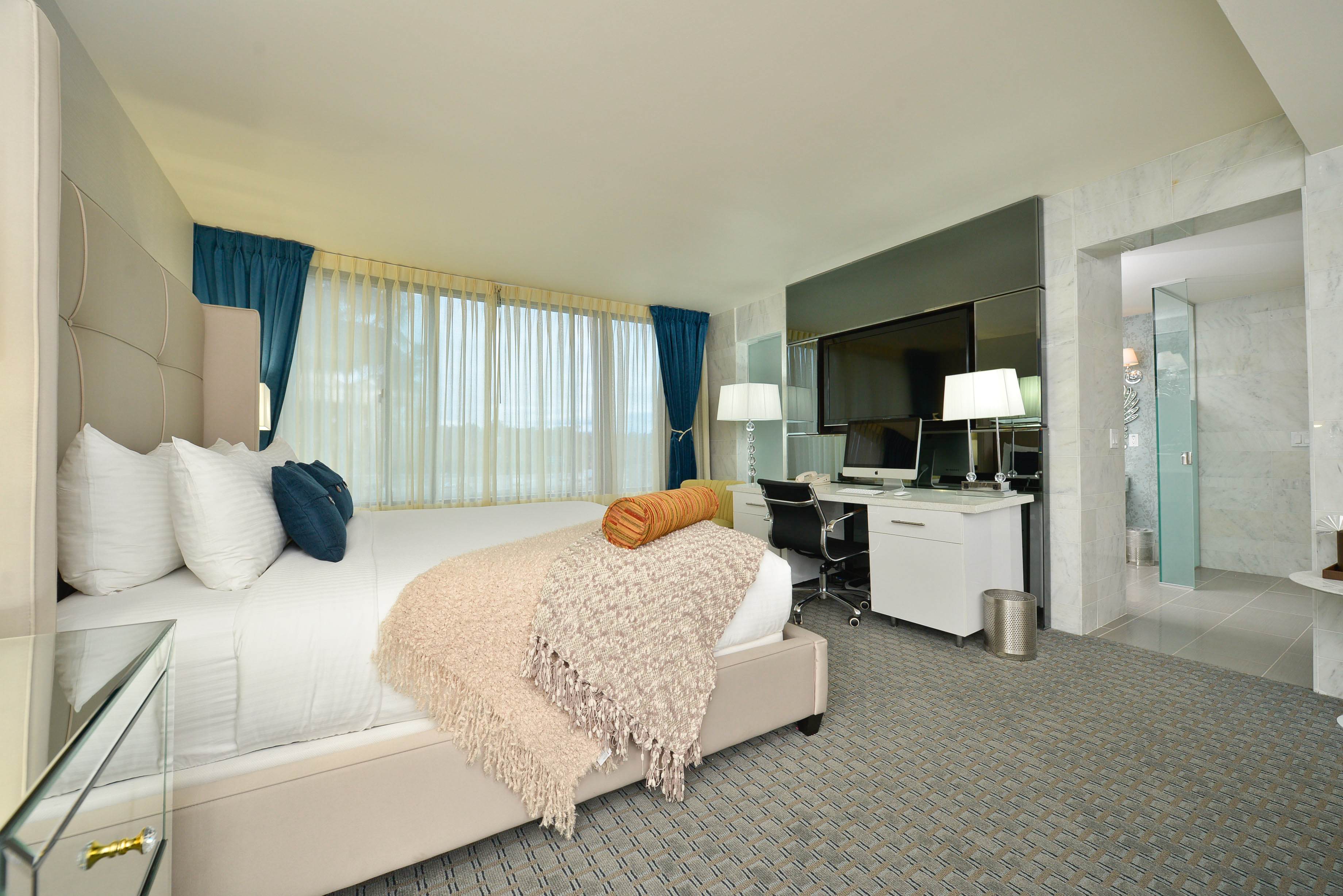 spacious guestroom with white and cream bedding large windows