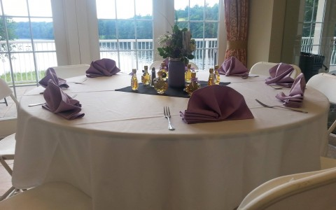 banquet table with purple napkins near window overlooking river