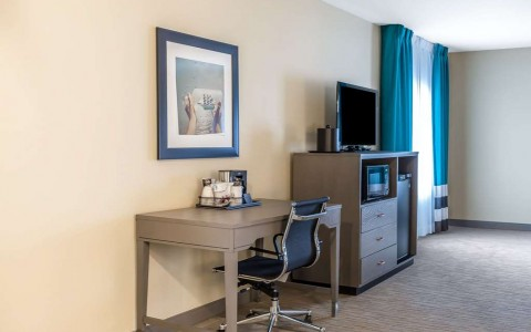 desk and chair in suite with tv