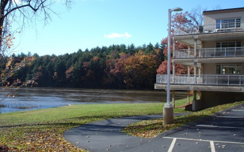 view of hotel balconies and river during fall time with orange and red leaves