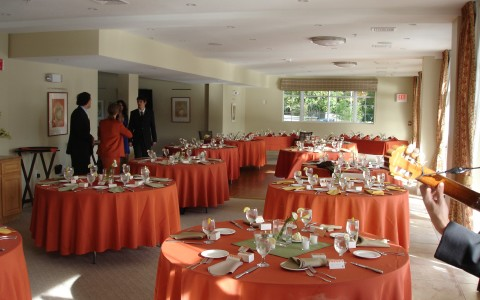 event space set up with orange clothed banquet tables