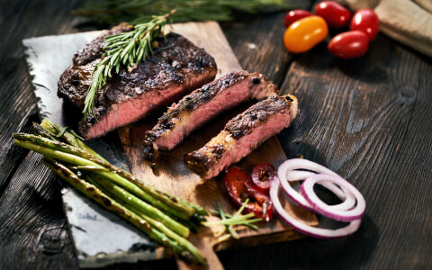 a steak with asparagus on a wood cutting board