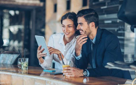 man and woman sitting at bar looking at tablet