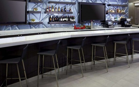 modern cocktail bar with seating and televisions
