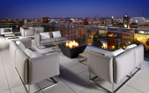 hotel rooftop with seating and fire pit with view of city
