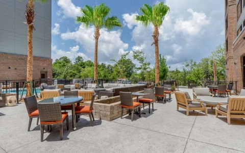 sundeck under palm trees with orange lounge chairs