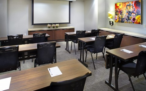 meeting room set up classroom style with projector screen