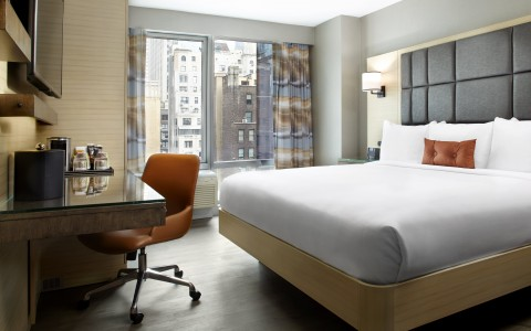 king bed in suite with view of new york city