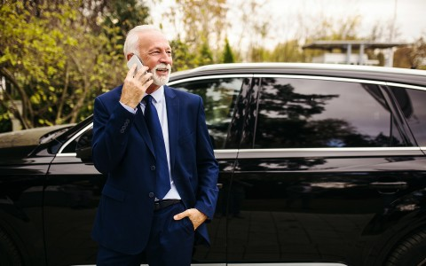 man in suit standing outside of car on the phone