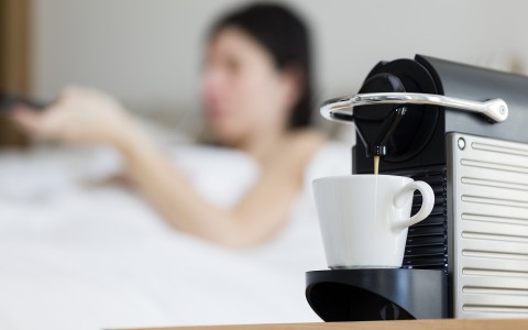 focused view of a nespresso machine with a woman in bed behind