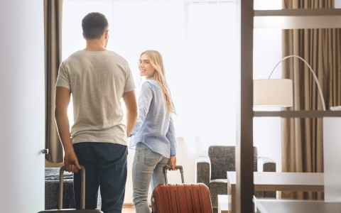couple walking into suite with luggage