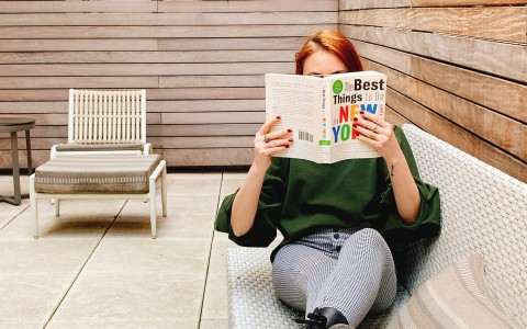 woman sitting on patio sofa reading book