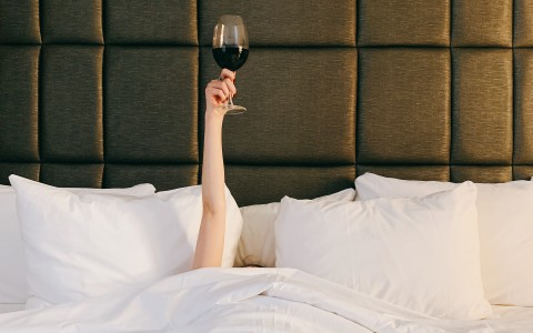 person laying in bed holding up glass of wine