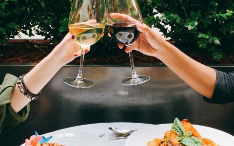 two girls clinking wine glasses over a seafood lunch