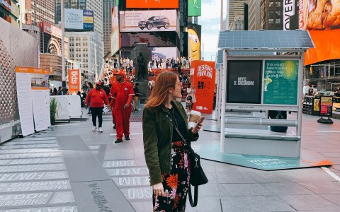 woman posing candidly in times square holding coffee cup