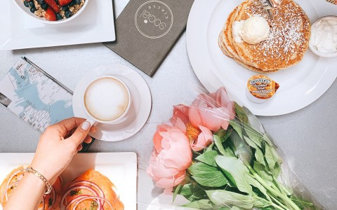 overhead shot of pancakes, lox, fruit and granola, coffee, and flowers