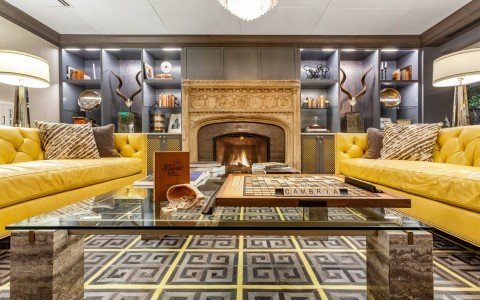 lobby with yellow sofas, fireplace, and game of scrabble on table