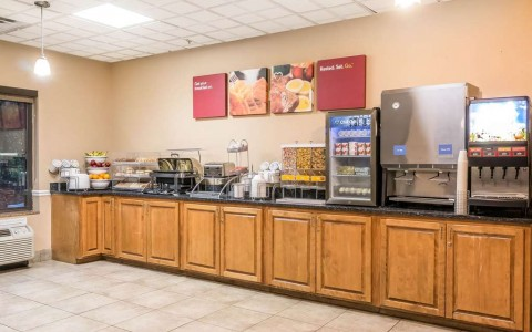 Breakfast counter with fruit, cereal, bakery items, hot food, and drinks