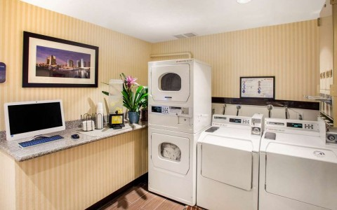 two washers and dryers in guest laundry facility along with computer