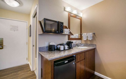 kitchenette area with mini fridge, coffee maker, microwave, and sink