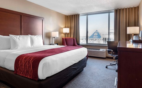 king size bed in room with a large window with a view of memphis