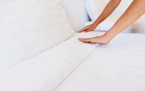 person making bed with white sheets