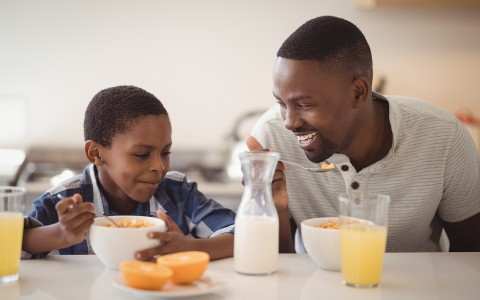 father and son eating cereal for breakfast with orange juice