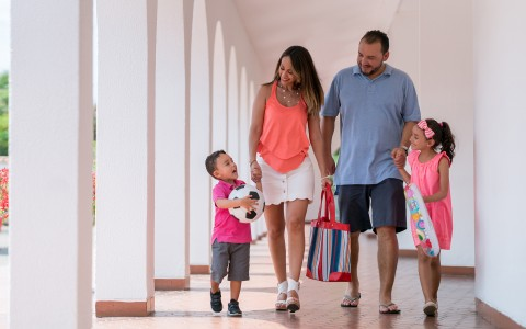 family of four walking through corridor outside of hotel