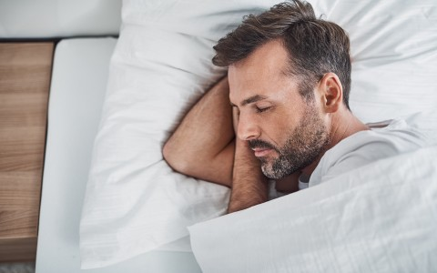 man sleeping in bed with white sheets