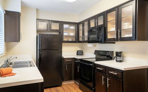kitchen in suite with fridge, counters, sink, cabinets and microwave