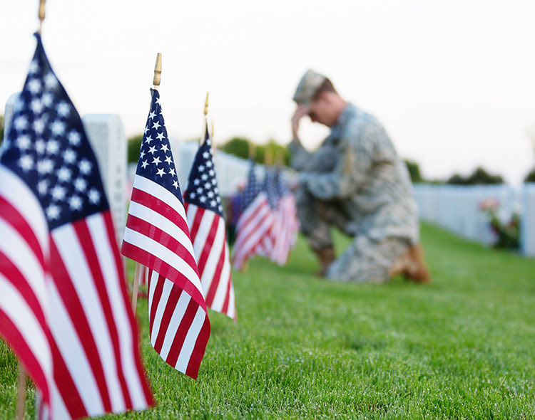 small american flags in ground at cemetery with a soldier kneeling at a gravesite