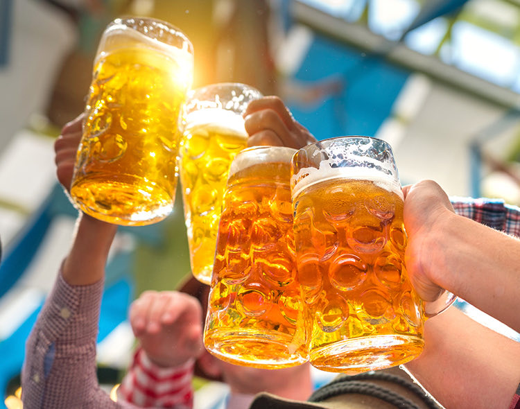 group of people raising up their large beer glasses to cheers