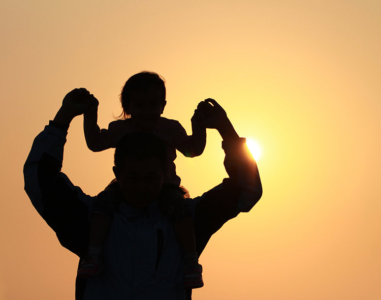father holding child on shoulders during sunset