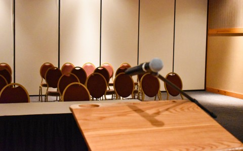 wooden podium with microphone staring out at a row of chairs
