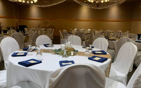 venue space with round tables with white cloths and place settings