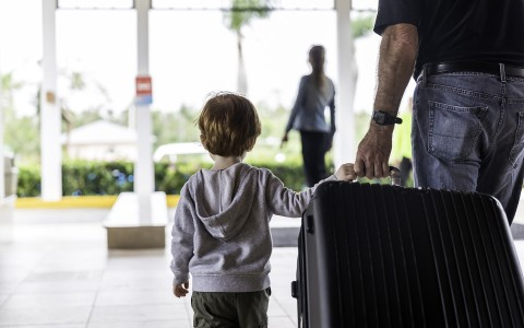 kid and his dad walking and pulling a large suitcase